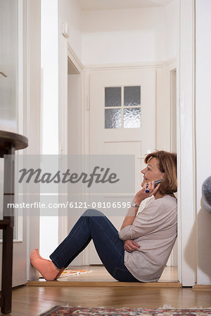 Profile shot of senior woman talking on mobile phone at doorway, Munich, Bavaria, Germany Stock Photo - Premium Royalty-Free, Image code: 6121-08106595