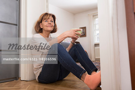 Senior woman having cup of tea at doorway, Munich, Bavaria, Germany Stock Photo - Premium Royalty-Free, Image code: 6121-08106596