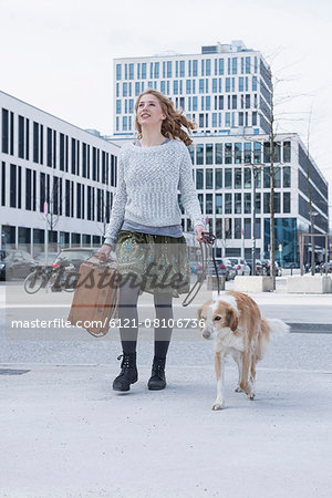 Young woman walking on road with dog and suitcase, Munich, Bavaria, Germany Stock Photo - Premium Royalty-Free, Image code: 6121-08106736