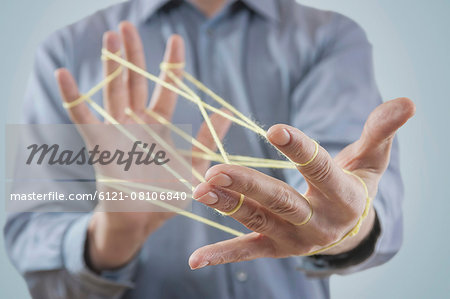 Mid section view of a man's hands making a cats cradle with string, Bavaria, Germany Stock Photo - Premium Royalty-Free, Image code: 6121-08106840