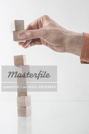 Man's hand stacking wooden building blocks, Bavaria, Germany Stock Photo - Premium Royalty-Free, Image code: 6121-08106843