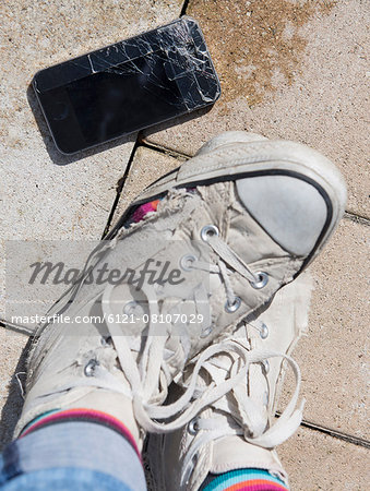 Person's leg with torn canvas shoes and cracked smartphone, Bavaria, Germany Stock Photo - Premium Royalty-Free, Image code: 6121-08107029