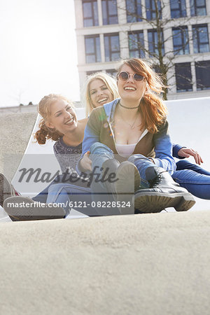 Three friends sliding down slide in a playground, Munich, Bavaria, Germany Stock Photo - Premium Royalty-Free, Image code: 6121-08228524