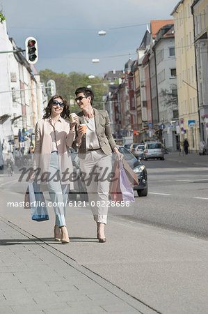 Two mature women shopping in the city with coffee, Bavaria, Germany Stock Photo - Premium Royalty-Free, Image code: 6121-08228658