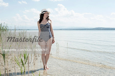 Mature woman walking in swimsuit at lake, Bavaria, Germany Stock Photo - Premium Royalty-Free, Image code: 6121-08228747