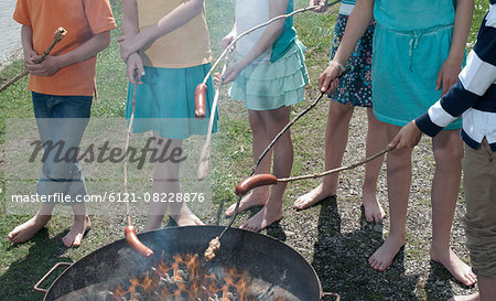 Group of friends preparing sausages on campfire, Bavaria, Germany Stock Photo - Premium Royalty-Free, Image code: 6121-08228876