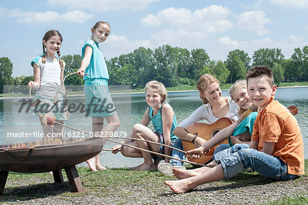 Group of friends preparing sausages on camp fire, Bavaria, Germany Stock Photo - Premium Royalty-Free, Image code: 6121-08228879