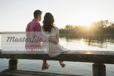Mature couple sitting on pier looking at sunset, Bavaria, Germany Stock Photo - Premium Royalty-Free, Image code: 6121-08361570