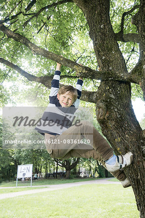 Boy climbing on tree and smiling, Munich, Bavaria, Germany Stock Photo - Premium Royalty-Free, Image code: 6121-08361620