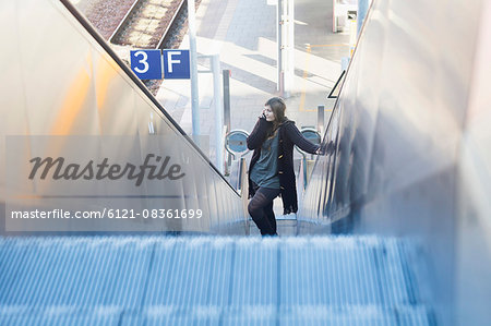 Young woman moving on escalator and talking on phone at railway station, Freiburg im Breisgau, Baden-Württemberg, Germany Stock Photo - Premium Royalty-Free, Image code: 6121-08361699