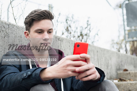 Young man text messaging on smart phone, Munich, Bavaria, Germany Stock Photo - Premium Royalty-Free, Image code: 6121-08522150