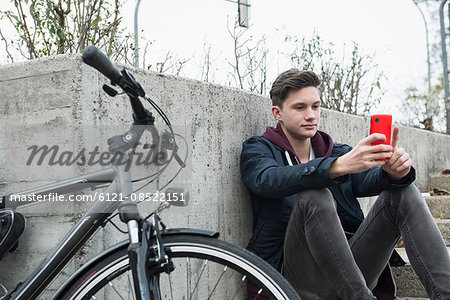 Young man text messaging on mobile phone and leaning against wall, Munich, Bavaria, Germany Stock Photo - Premium Royalty-Free, Image code: 6121-08522151