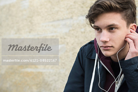 Close-up of young man listening to music with earbud, Munich, Bavaria, Germany Stock Photo - Premium Royalty-Free, Image code: 6121-08522167