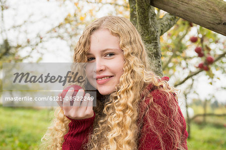 Portrait of a blond teenage girl eating an apple in an apple orchard farm, Bavaria, Germany Stock Photo - Premium Royalty-Free, Image code: 6121-08522249