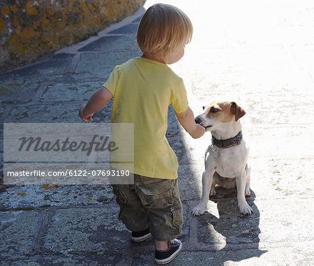 Baby boy playing with a dog Stock Photo - Premium Royalty-Free, Image code: 6122-07693190