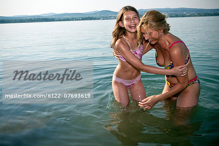 Mother and daughter laughing in lake Stock Photo - Premium Royalty-Free, Image code: 6122-07693619