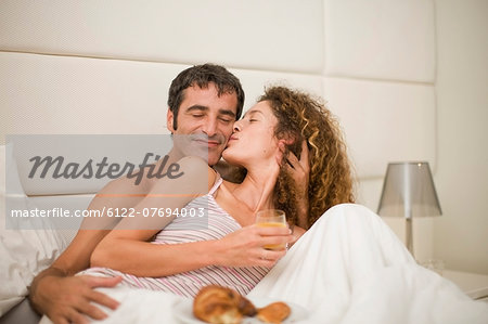 Smiling couple having breakfast in bed Stock Photo - Premium Royalty-Free, Image code: 6122-07694003