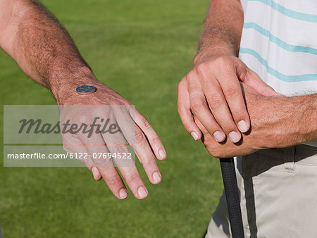 Two mature men playing golf together, tossing a coin Stock Photo - Premium Royalty-Free, Image code: 6122-07694522