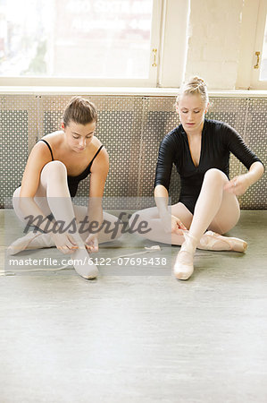 Ballerinas putting on ballet slippers Stock Photo - Premium Royalty-Free, Image code: 6122-07695438
