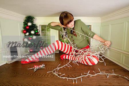 Young woman in small room with christmas lights Stock Photo - Premium Royalty-Free, Image code: 6122-07695442