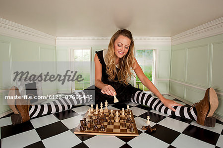 Young woman in small room with chess set Stock Photo - Premium Royalty-Free, Image code: 6122-07695443