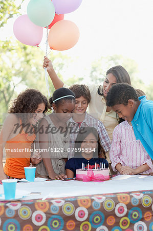 Children at birthday party with birthday cake Stock Photo - Premium Royalty-Free, Image code: 6122-07695534