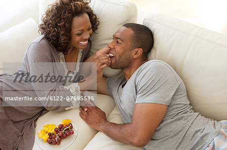 Woman feeding grapes to boyfriend Stock Photo - Premium Royalty-Free, Image code: 6122-07695595