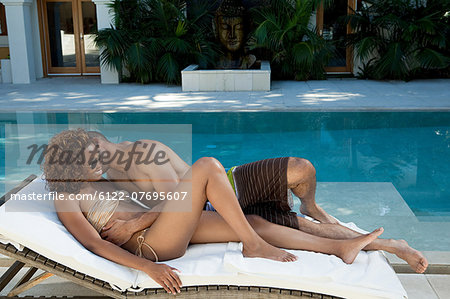 Loving couple on lounger by pool Stock Photo - Premium Royalty-Free, Image code: 6122-07695607