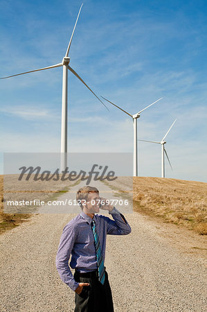 Man using mobile phone in front of wind turbines Stock Photo - Premium Royalty-Free, Image code: 6122-07697706