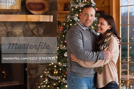 Mature couple embracing by Christmas tree, portrait Stock Photo - Premium Royalty-Free, Image code: 6122-07697821