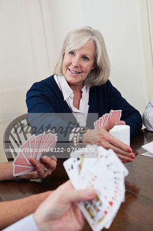 Mature woman playing cards Stock Photo - Premium Royalty-Free, Image code: 6122-07697873