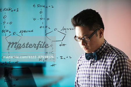 Young man with diagram on window Stock Photo - Premium Royalty-Free, Image code: 6122-07698176