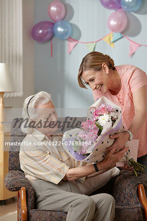 Daughter giving senior mother bouquet of flowers Stock Photo - Premium Royalty-Free, Image code: 6122-07698194