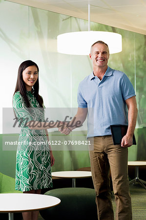 Mature man shaking hands with young woman in meeting Stock Photo - Premium Royalty-Free, Image code: 6122-07698421