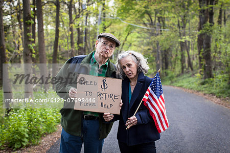 Senior couple holding sign in forest, portrait Stock Photo - Premium Royalty-Free, Image code: 6122-07698446