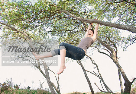 Girl swinging from tree outdoors Stock Photo - Premium Royalty-Free, Image code: 6122-07698960