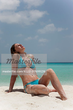 Woman sitting in sand on tropical beach Stock Photo - Premium Royalty-Free, Image code: 6122-07699136