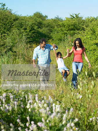Family walking in field of flowers Stock Photo - Premium Royalty-Free, Image code: 6122-07699251