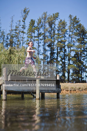 Boy jumping into lake from jetty Stock Photo - Premium Royalty-Free, Image code: 6122-07699456