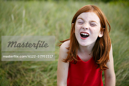 Girl grimacing in tall grass Stock Photo - Premium Royalty-Free, Image code: 6122-07702317