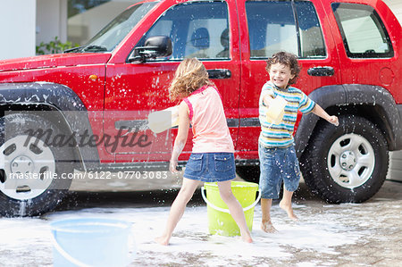 Children playing and washing car Stock Photo - Premium Royalty-Free, Image code: 6122-07703083