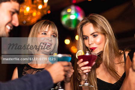 Smiling women having cocktails in club Stock Photo - Premium Royalty-Free, Image code: 6122-07703123