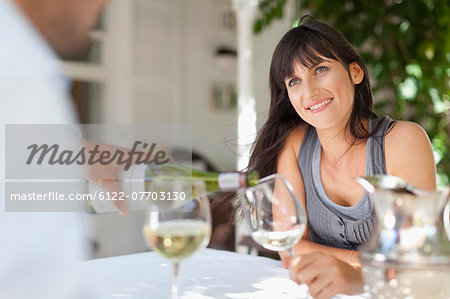 Couple having wine at table outdoors Stock Photo - Premium Royalty-Free, Image code: 6122-07703130