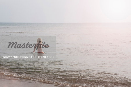 Child wading nude in ocean Stock Photo - Premium Royalty-Free, Image code: 6122-07703282