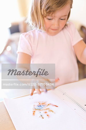 Girl finger-painting in notebook Stock Photo - Premium Royalty-Free, Image code: 6122-07703434