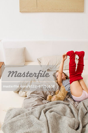 Girl getting dressed on bed Stock Photo - Premium Royalty-Free, Image code: 6122-07703518