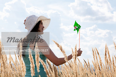 Woman holding pinwheel in wheatfield Stock Photo - Premium Royalty-Free, Image code: 6122-07703527