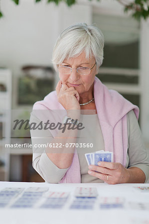 Older woman playing cards Stock Photo - Premium Royalty-Free, Image code: 6122-07703560