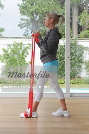 Older woman using exercise band at home Stock Photo - Premium Royalty-Free, Image code: 6122-07703693