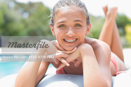 Teenage girl in braces relaxing by pool Stock Photo - Premium Royalty-Free, Image code: 6122-07703982